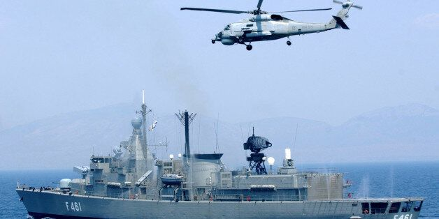 The Greek frigate Navarino, and a helicopter, conduct a security exercise on the Saronic Gulf, south...