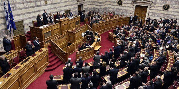 Greek lawmakers applaud at the end of the vote for a president at the Greek parliament in Athens, on...