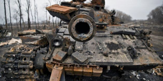 A destroyed tank is abandoned on the road at a former Ukrainian army checkpoint that was overran last...