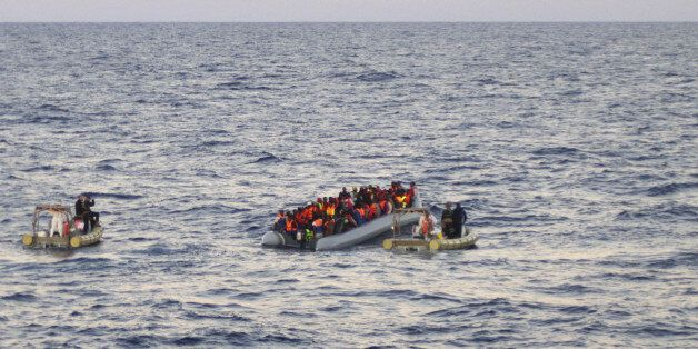 In this file photo taken on Thursday, Dec. 4, 2014 provided by the Italian Navy, rescue crews approach...