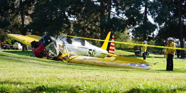 Officials work on the scene of a vintage airplane that crash-landed on the Penmar Golf Course in the...