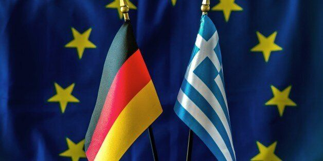 A picture taken on February 23, 2015 shows a German (L) and a Greek flag against a backdrop of a European...