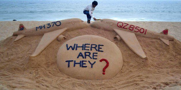 Indian sand artist Sudarsan Pattnaik gives the final touches to his sand sculpture portraying two missing...