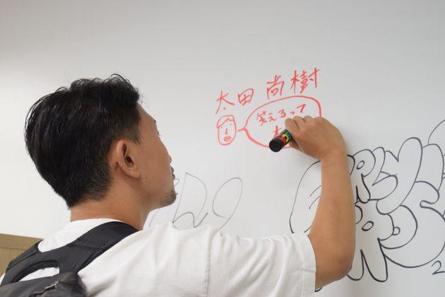 太田尚樹さん。ハフポスト日本版のオフィスの壁に「笑えるって大事」とメッセージを書いてくれた
