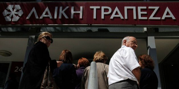People wait outside of a branch of Laiki bank in Nicosia, Thursday, March 28, 2013. Banks in Cyprus reopened...