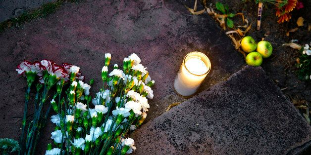 BOULDER, CO - AUGUST 11: Flowers and a single candle are left at a makeshift memorial for Robin Williams...