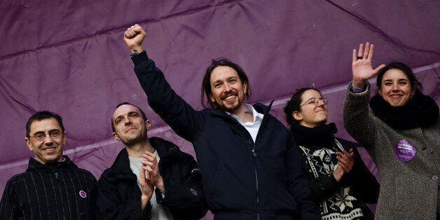 Pablo Iglesias, center, leader of Spanish Podemos (We Can) left-wing party, raises his fist on the stage...