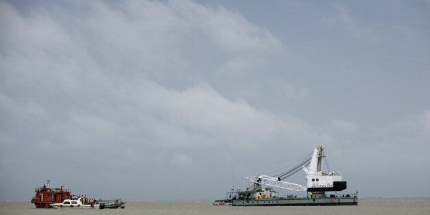 Bangladeshi rescue teams search the waters where an overloaded ferry capsized the day before in the Padma...