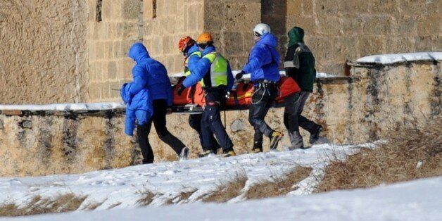 French rescuers carry on January 25, 2015 in church of Ceillac the body of one of six skiers victims...