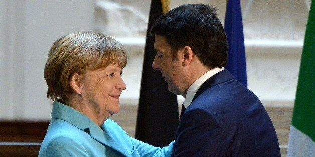 Italian Prime Minister Matteo Renzi (R) hugs German Chancellor Angela Merkel beneath the original 16th...