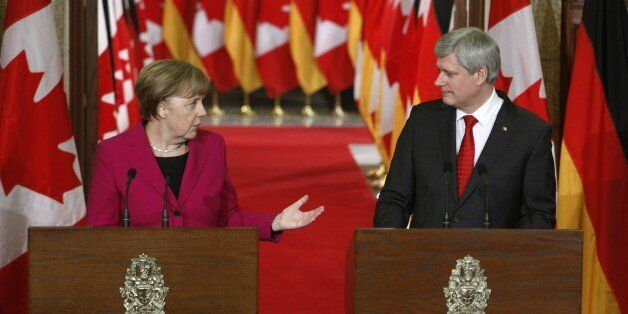 Chancellor Angela Merkel (L) and Canadian Prime Minister Stephen Harper (R) speak at a joint press conference...