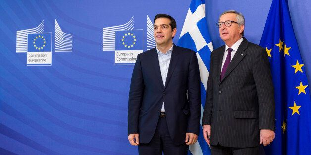European Commission President Jean-Claude Juncker, right, stands with Greece's Prime Minister Alexis...