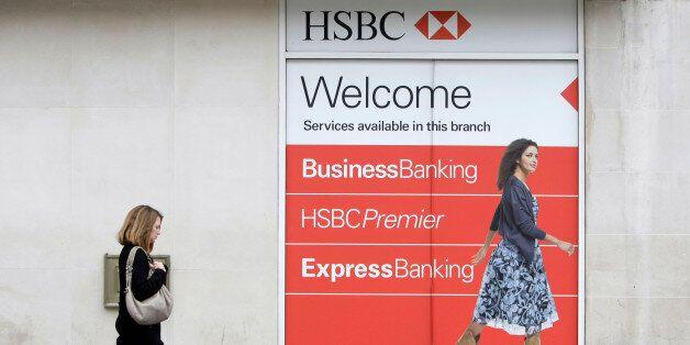 ARCHIV - Eine Frau laeuft am 10. November 2009 in London an einer Werbung fuer die HSBC-Bank vorbei....
