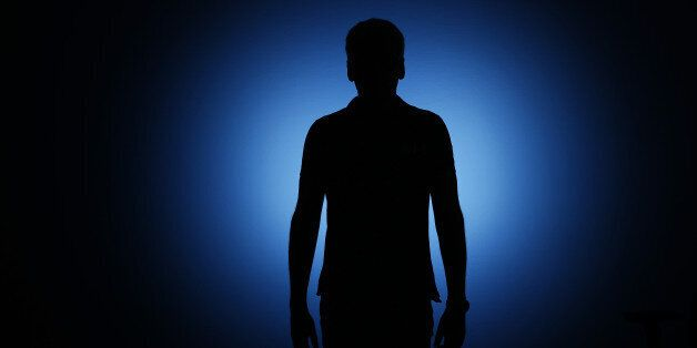 BERLIN, GERMANY - AUGUST 06: Silhouette of a man standing in front of a blue background on August 06,...