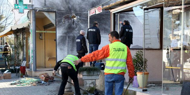 Police officers check the site of an explosion at a drug store, left, belonging to Interior Minister...
