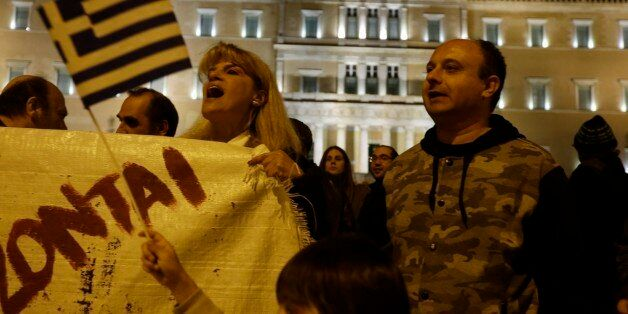 Protesters wave a Greek flag and shout slogans during an anti-austerity rally outside the Greek Parliament...