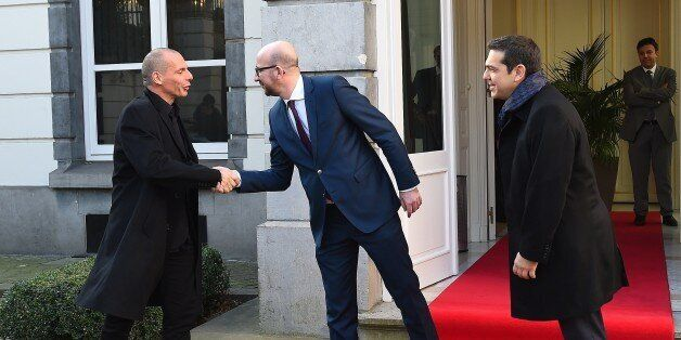 Belgian Prime Minister Charles Michel (C) welcomes Greek Finance Minister Yanis Varoufakis (L) and Greek...