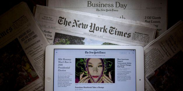 An Apple Inc. iPad displays the New York Times application (app) while sitting on New York Times newspapers...