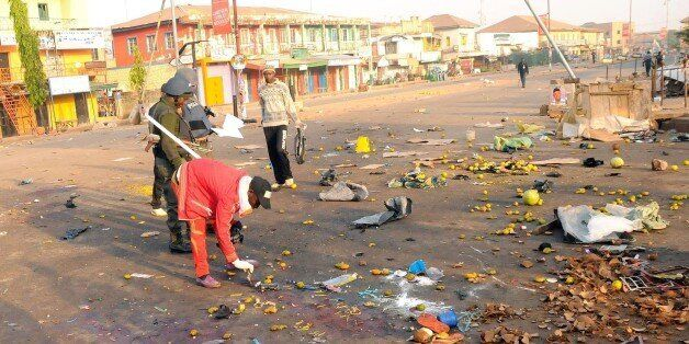 Nigerian security inspect the scene of a bomb blast at the Jos Terminus Market, on December 12, 2014....