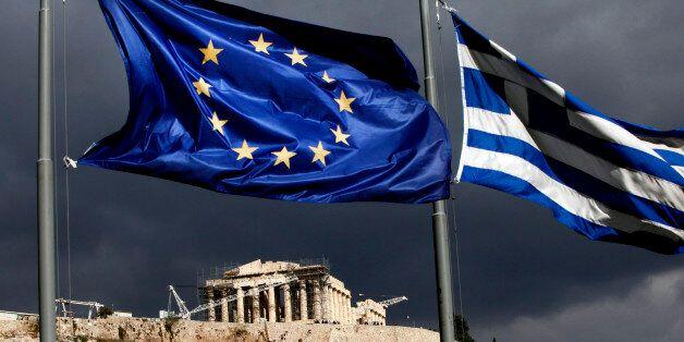 A European Union (EU) flag, left, and Greek national flag fly near the Parthenon temple on Acropolis...