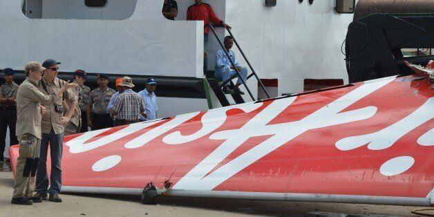 Foreign investigators (L) examine the tail of the AirAsia flight QZ8501 in Kumai on January 12, 2015,...