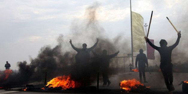FILE - In this Monday, Dec. 30, 2013, file photo, Iraqi Sunni masked protesters burn tires to block the...
