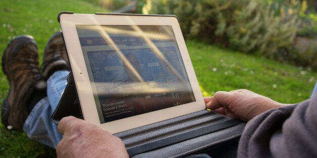 A man watches basketball on his iPad while sitting outside in his garden in the