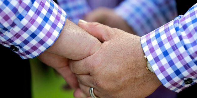 Alberto Molina-Coats, right, holds hands with his new spouse Glenn Molina-Coats during a mass same-sex...