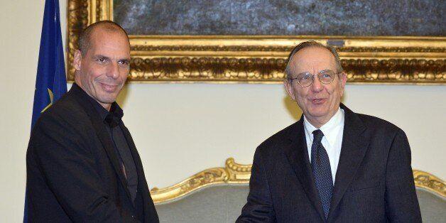 Greek Minister of Finance Yanis Varoufakis (L) shakes hands with his Italian counterpart Pier Carlo Padoan...