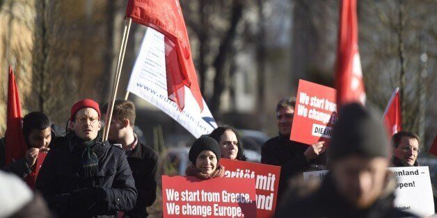 Protestors hold a sign reading 'We start from Greece, we change Europe' during a demonstration in front...