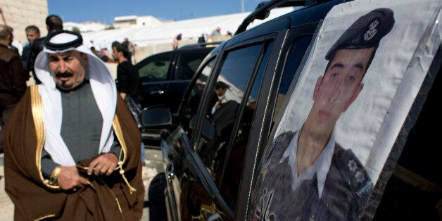 A Jordanian man walks past a poster that is pasted on a vehicle with a picture of slain Jordanian pilot,...