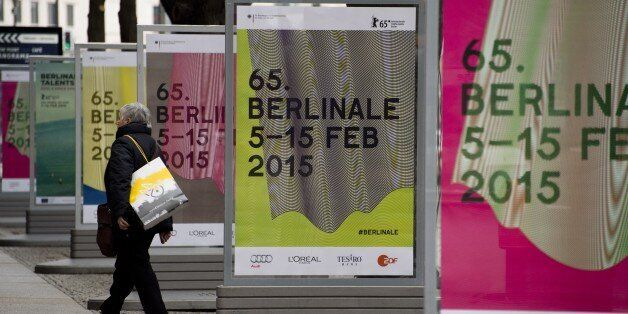 A woman walks by bildboards featuring ad for the 65th edition of the Berlinale Film Festival on the Potsdamer...