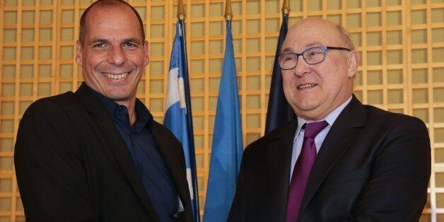 Greek Finance Minister Yanis Varoufakis (L) shakes hands with his French counterpart Michel Sapin after...