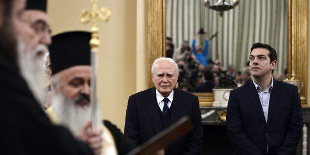 Newly elected Greek Prime Minister Alexis Tsipras (R) and President Carolos Papaoulias look on as the...