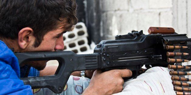 In this Wednesday, Nov. 19, 2014 photo, a young Kurdish People's Protection Units (YPG) fighter who recently...