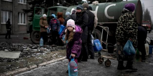 A girl holds a water bottle in the town of Debaltseve, eastern Ukraine, Friday, Feb. 6, 2015. Pro-Russia...