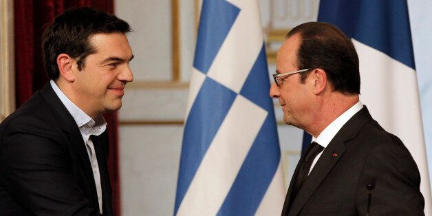 Greece's Prime Minister Alexis Tsipras, left, and French President Francois Hollande, shake hands after...
