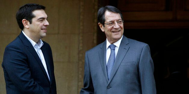Cyprus' president Nicos Anastasiades, right, shakes hands with Greek Prime Minister Alexis Tsipras at...