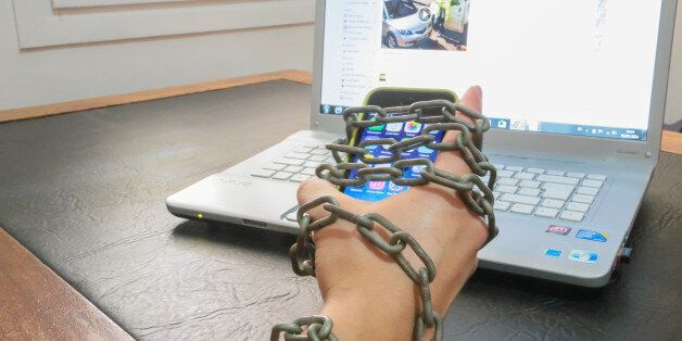 Guy chained to smartphone and internet laptop. Conceptual picture for internet