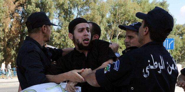 Algerian policemen arrest a demonstrator during a protest against an amateur film mocking Islam in Algiers...