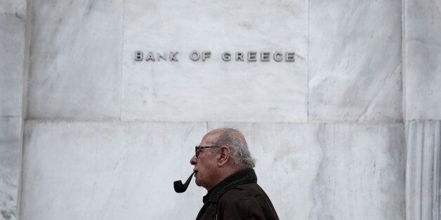 A man walks past the Bank of Greece headquarters, in central Athens, on Wednesday, Feb. 4, 2015. With...