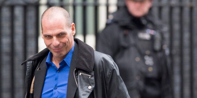 Yanis Varoufakis, Greece's finance minister, left, passes a police officer as he arrives for his meeting...