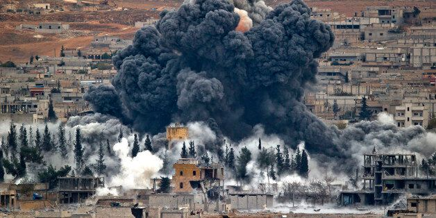 FILE - In this Monday, Nov. 17, 2014 file photo, smoke rises from the Syrian city of Kobani, following...