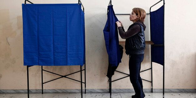 A municipal worker assembles voting booths at a voting center, in Athens, Friday, Jan. 23, 2015. Prime...