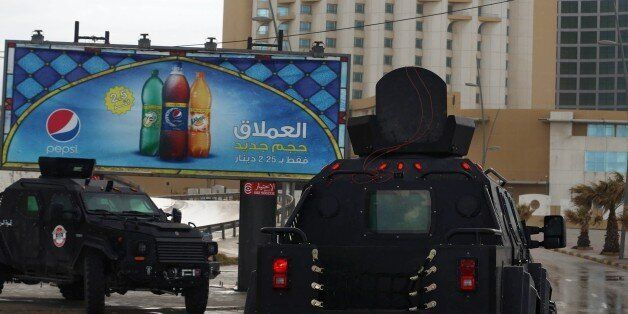 Libyan security forces surround Tripoli's central Corinthia Hotel (R) on January 27, 2015 in the Libyan...