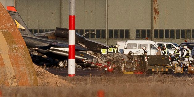 Investigators work around the wreckage of planes the day after a crash at Albacete airbase, Spain, Tuesday,...