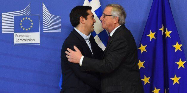 European Commission President Jean-Claude Juncker (R) greets Greek Prime Minister Alexis Tsipras at the...