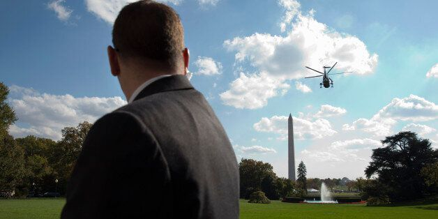 A Secret Service agent watches as Marine One carries President Barack Obama from the South Lawn of the...