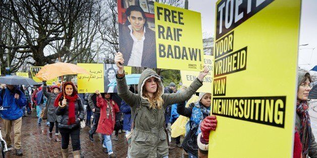 People take part in a protest by Amnesty International, for the immediate release of the Saudi blogger...