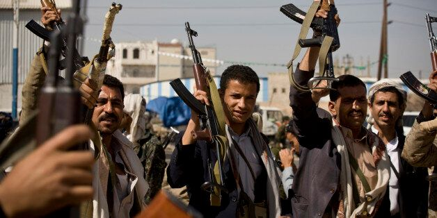 Houthi Shiite Yemeni hold their weapons during clashes in near the presidential palace in Sanaa, Yemen,...